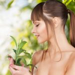 beauty and eco cosmetology concept - beautiful woman on nature with green sprout